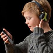 Ein Junge mit Kopfhörern schaut auf ein Smartphone, das er in seiner Hand hält.