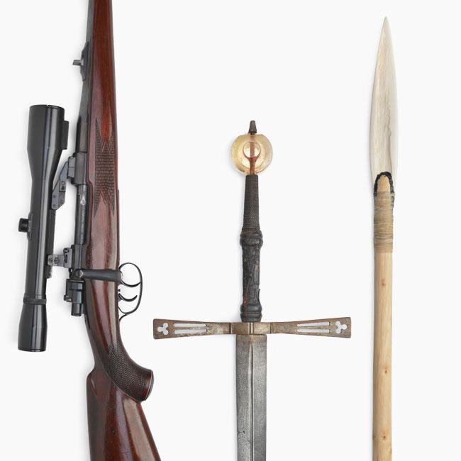 Ein Repetiergewehr, ein mittelalterliches Schwert und ein Speer.